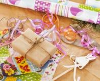 La porción de materia para los regalos hechos a mano, tijeras, cinta, papel con el modelo del campo, alista para el concepto del  Imagenes de archivo