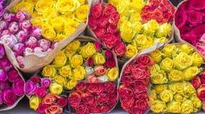 La porción de ramos amarillos, rosados, rojos subió con la envoltura en el mercado Foto de archivo