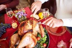 La porción del viejo hombre del primer asó el pavo en un fondo de la tabla Cena de la acción de gracias Concepto festivo tradicio Imagen de archivo