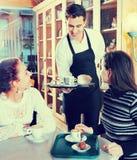 La porción positiva de la camarera se apelmaza y los pasteles para las muchachas fotografía de archivo libre de regalías