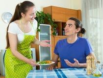 La porción cariñosa de la mujer almuerza su hombre en la tabla Fotografía de archivo libre de regalías