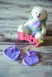 La porpora ha tricottato i calzini del bambino con un'iscrizione di un bambino e di una lepre del giocattolo su un fondo di legno Fotografia Stock