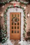 La porta alla casa con il Natale si avvolge Fotografie Stock