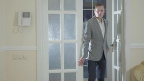 La porta di apertura sicura dell'agente immobiliare che entra nella nuova casa di lusso, mostra ad una giovane riuscita coppia sp stock footage