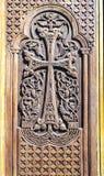 La porta di legno della chiesa con l'incrocio scolpito ha montato del modello floreale piega Fotografie Stock