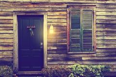 La porta e la finestra rustiche con gli otturatori chiusi ed il portico si accendono Immagine Stock