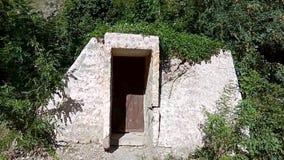 La porta e la parete molto vecchie della pietra dell'entrata in foresta all'aperto hanno sviluppato la struttura di vecchia casa  stock footage