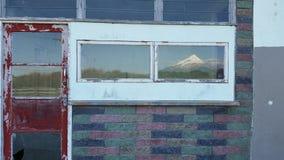 La porta rossa della parete di Bricked con il Mt Taranaki ha riflesso in finestra Fotografia Stock