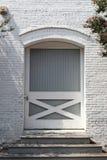 La porte arquée sur un vieux bâtiment commercial avec les étapes et le blanc en bois a peint la brique Image stock