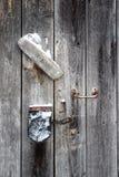 La porte avec la poignée et le cadenas rouillés Photo libre de droits