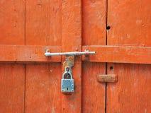 La porte en bois de vintage est une couleur orange lumineuse, fermée sur un verrou en métal et un cadenas antique Images libres de droits
