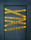 La porte fermée par scène du crime avec la ligne de police jaune des textes de rayures ne croisent pas photos stock