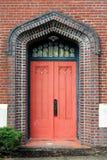 La porte rouge fanée fleurie a placé dans le mur de briques coloré Photo libre de droits