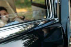 la portière de voiture par la fenêtre qui est les personnes évidentes qui se situent dans la voiture et tiennent des mains Image libre de droits