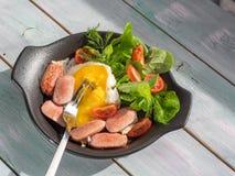 La portion a fraîchement fait cuire le petit déjeuner nutritif des oeufs brouillés et des saucisses, servant dans une poêle noire photos libres de droits