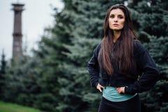 La posa di riposo della bella di forma fisica donna castana dell'atleta dopo risolve l'esercitazione al parco Fotografie Stock