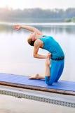 La posa ibrida di yoga del Backbend della rana del cammello ha praticato alla sponda del fiume Fotografie Stock Libere da Diritti