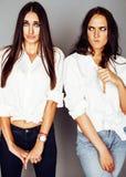 La pose de fille de deux jumelles de soeurs, faisant le selfie de photo, a habillé la même chemise blanche, amis divers de coiffu Photographie stock libre de droits