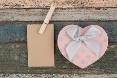 La pose de papier peint de Brown sur la corde à linge et boîte-cadeau de coeur sur le bois de vintage Image stock