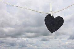 La pose de papier peint noire de coeur sur une corde brune de chanvre sur le Ba de nuages de pluie Image libre de droits