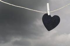 La pose de papier peint noire de coeur sur une corde brune de chanvre sur le Ba de nuages de pluie Photos libres de droits