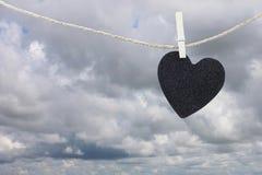 La pose de papier peint noire de coeur sur une corde brune de chanvre sur le Ba de nuages de pluie Photo stock