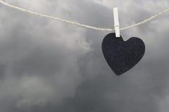 La pose de papier peint noire de coeur sur une corde brune de chanvre sur le Ba de nuages de pluie Images stock