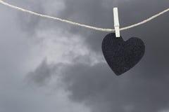 La pose de papier peint noire de coeur sur une corde brune de chanvre sur le Ba de nuages de pluie Photographie stock libre de droits