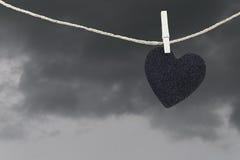 La pose de papier peint noire de coeur sur une corde brune de chanvre sur le Ba de nuages de pluie Photo libre de droits