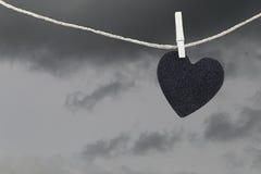 La pose de papier peint noire de coeur sur une corde brune de chanvre sur le Ba de nuages de pluie Photos stock