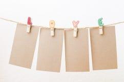 La pose de papier peint vide sur la corde à linge d'amour avec le fond blanc Images libres de droits