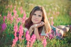La pose sexy d'offre de poils foncés de brune de femme adorable avec du charme de jeune dame et de yeux verts avec des fleurs tre Photos libres de droits