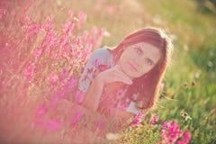 La pose sexy d'offre de poils foncés de brune de femme adorable avec du charme de jeune dame et de yeux verts avec des fleurs tre Images libres de droits