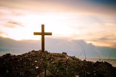 La position croisée sur le coucher du soleil de pré et le fond de fusée La croix sur une colline comme soleil de matin est soulev Images stock