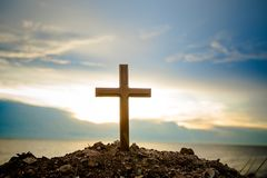 La position croisée sur le coucher du soleil de pré et le fond de fusée La croix sur une colline comme soleil de matin est soulev Image stock