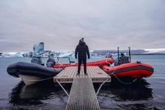 La position d'homme sur le pilier en hiver Vêtements élégants d'hiver Icebergs dans la lagune de Jokulsarlon photos libres de droits