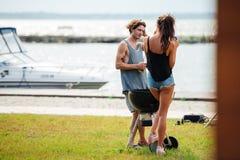 La position de couples et le rassemblement de faire frire sur le barbecue grillent dehors Photo libre de droits