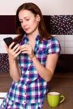 La position de femme et écrivent à son téléphone portable photos stock