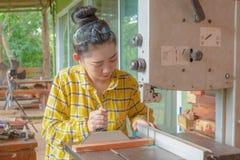 La position de femmes est métier fonctionnant le bois coupé à un banc de travail photo libre de droits