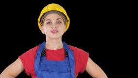 La position de sourire de femme de travailleur de constructeur et les poses changeantes plient les mains, les mains sur des hanch banque de vidéos