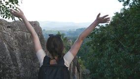 La position de touristes de femme au bord du beau canyon, tendant victorieusement arme  Jeune randonneur féminin avec images libres de droits