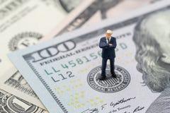 La position miniature de chef d'homme d'affaires et la pensée sur l'emblème de Réserve fédérale américaine sur le billet de banqu photo libre de droits