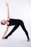 La posizione avanzata di yoga, dimostrata vicino bloden la ragazza, vestita nel nero, su fondo bianco Fotografia Stock Libera da Diritti