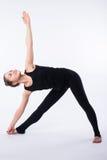 La posizione avanzata di yoga, dimostrata vicino bloden la ragazza, vestita nel nero, su fondo bianco Immagini Stock Libere da Diritti