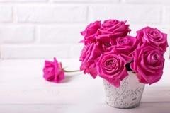 La postal con las rosas rosadas brillantes florece en el backg de madera blanco Foto de archivo
