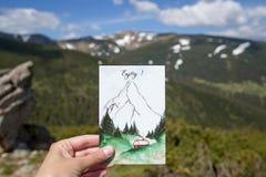 La postal del viaje en la mano con el fondo de montañas, aventuras en las montañas, disfruta del momento imagen de archivo libre de regalías