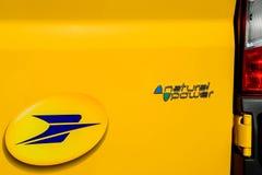 La Poste-Firmenzeichen nahe bei natürlichem Energiezeichen Lizenzfreie Stockbilder