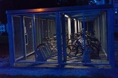 La postura de la bicicleta en la noche cerrada abajo con el againt de la cerca roba robos robados de las bicis Imágenes de archivo libres de regalías