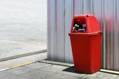 La poubelle en plastique, l'extérieur rouge de poubelle aux feuilles de zinc de mur, rouge de poubelle pour réutilisent les déche image stock