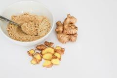 La poudre de gingembre dans la cuvette avec la cuillère en métal, la racine de gingembre et le gingembre rapièce en dehors de la  Images stock